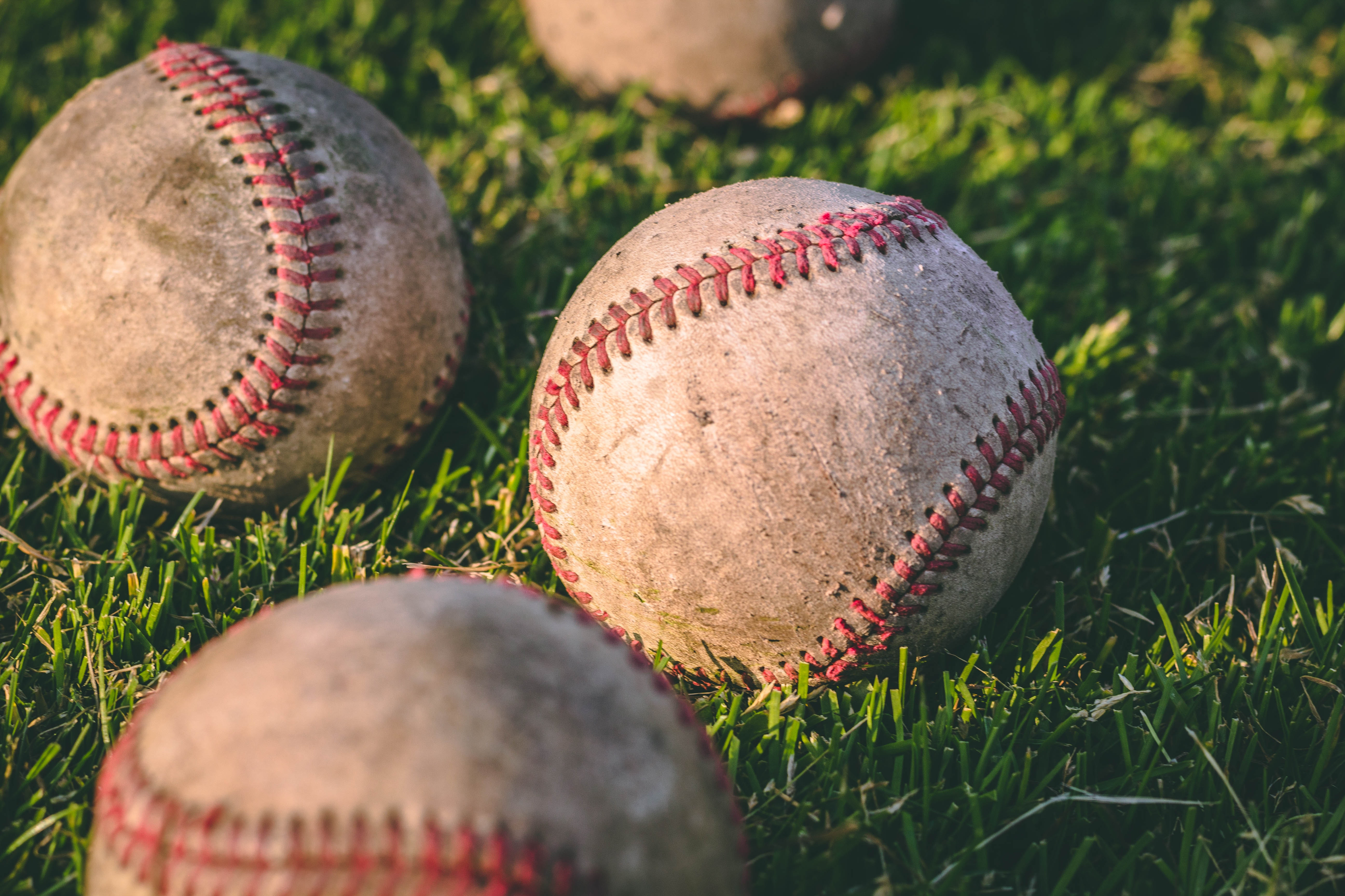 close-up-photography-of-four-baseballs-on-green-lawn-grasses-1308713